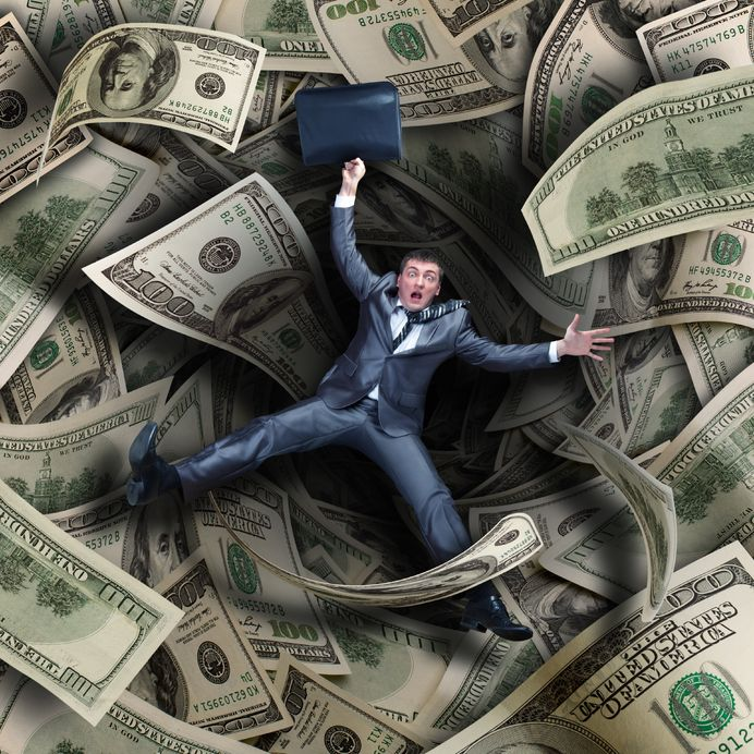 20310312 - businessman falling into tunnel of $100 dollar bills